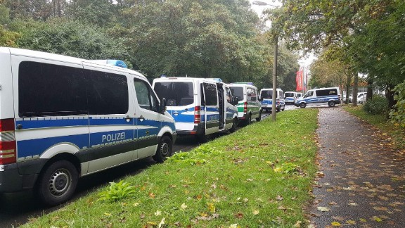 Police vehicles are lined up in front of an apartment building Saturday in Chemnitz
