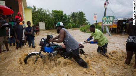 Men push a motorbike through a flooded street in Leogane on Wednesday, October 5.