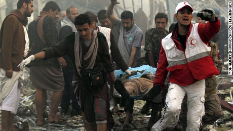 Yemeni rescue workers carry a victim on a stretcher amid the rubble of a destroyed building following reported airstrikes by Saudi-led coalition air-planes on the capital Sanaa on October 8, 2016.