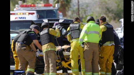 Emergency personnel wearing bullet-proof vests attend to a person on a stretcher on the corner of Cypress Road and Del Lago Road in Palm Springs, Calif. on Saturday, Oct. 8, 2016. Palm Springs police say three officers had been shot but did not give their conditions. (Omar Ornelas/The Desert Sun via AP)