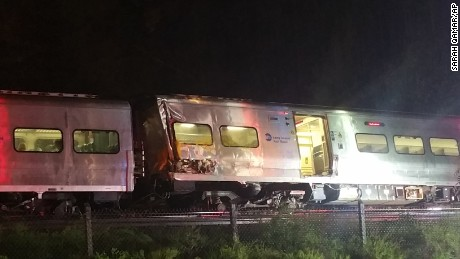 In this photo provided by Sarah Qamar shows a Long Island Railroad train derailed near New Hyde Park, N.Y., Saturday, Oct. 8, 2016.  The commuter train derailed east of New York City after it hit a work train on the tracks. A spokesman for the Long Island Rail Road says the eastbound train derailed east of New Hyde Park just after 9 p.m. Saturday. A spokeswoman for the Nassau County Police Department says there are 50 to 100 injuries, none of them life-threatening. (Sarah Qamar via AP)