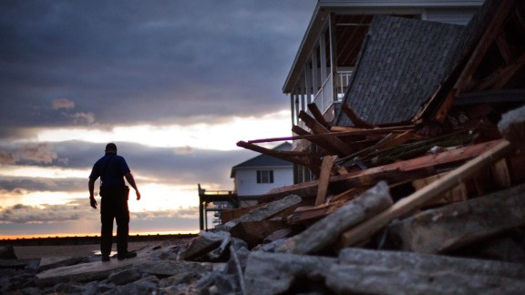 A police officer steps through the remnants of a home leveled by Hurricane Matthew in the tiny beach community of Edisto Beach, South Carolina, on October 8.