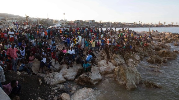 "Residents of Jeremie wait on the shore October 8 as a boat with water and food from the ""Mission of Hope"" charity arrives. Jeremie appears to be the epicenter of Haiti"