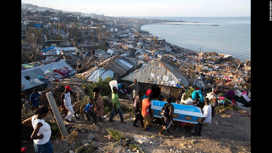 Residents carry a coffin containing the remains of a pregnant woman, a victim of Hurricane Matthew, in Jeremie on Friday, October 7. People across southwest Haiti were digging through the wreckage of their homes Friday, salvaging what they could of their meager possessions.