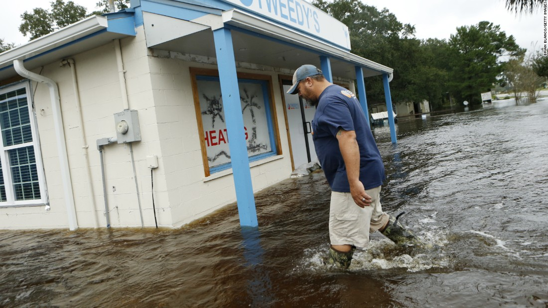 John Tweedy wades into the swift-moving floodwaters surrounding his business in McClellanville, South Carolina, on Saturday, October 8.