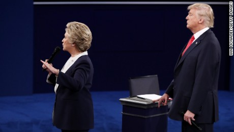Hillary Clinton speaks as Republican presidential nominee Donald Trump looks on during the town hall debate at Washington University on October 9 in St Louis, Missouri.