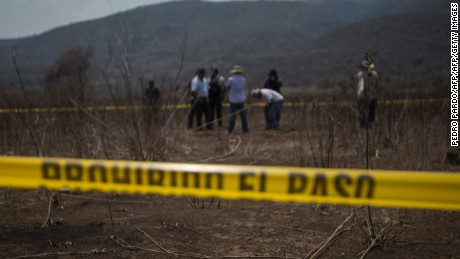Picture taken on May 19, 2016 showing a cordoned-off area near the small town of El Mirador alongside a road linking the Mexican towns of Coacoyula and Apipilulco, where bone fragments corresponding to an undetermined number of individuals were found on May 17. Skeletal remains from an undetermined number of individuals have been found not far from where 43 Mexican students went missing nearly two years ago, officials said late May 18. Investigators found bone fragments including skulls, shin bones, jawbones and teeth of various people, as well as sandals and pieces of clothing, according to a statement from the prosecutor's office in the impoverished southern state of Guerrero.  / AFP / Pedro Pardo        (Photo credit should read PEDRO PARDO/AFP/Getty Images)