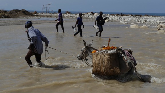 People cross one of the many southern coastal rivers where bridges were knocked out or damaged near Port-a-Piment on October 10.