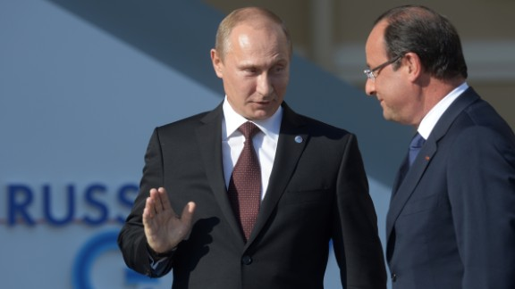 In this handout image provided by Host Photo Agency, Russian President Vladimir Putin stands with French President  Francois Hollande during an official welcome of G20 heads of state and government, heads of invited states and international organizations at the G20 summit on September 5, 2013 in St. Petersburg, Russia.  The G20 summit is expected to be dominated by the issue of military action in Syria while issues surrounding the global economy, including tax avoidance by multinationals, will also be discussed duing the two-day summit.