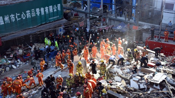 Rescuers search for survivors at an accident site after four buildings caved in during the early hours in Wenzhou, eastern China