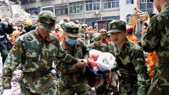 Rescuers carry an injured survivor on a stretcher at an accident site after  in Wenzhou, in China