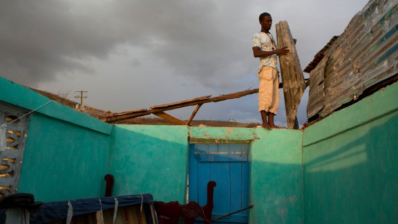 A man uses salvaged material to build a makeshift roof for his damaged house in Port-a-Piment on October 10.
