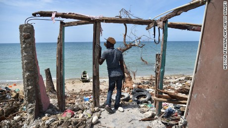 "TOPSHOT - A man stands next to a destroyed house in Les Cayes, Haiti on October 10, 2016, following the passage of Hurricane Matthew.  Haiti faces a humanitarian crisis that requires a ""massive response"" from the international community, the United Nations chief said , with at least 1.4 million people needing emergency aid following last week's battering by Hurricane Matthew. / AFP / HECTOR RETAMAL        (Photo credit should read HECTOR RETAMAL/AFP/Getty Images)"