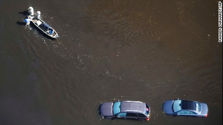 People wade in floodwaters with a boat Monday in Nichols, South Carolina.