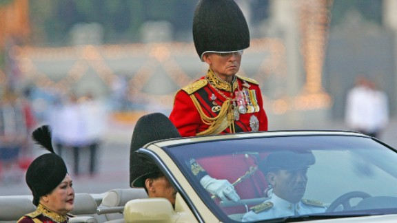 The King reviews an honor guard with Queen Sirikit and Crown Prince Vajiralongkorn during the annual military parade to celebrate his birthday in 2006.