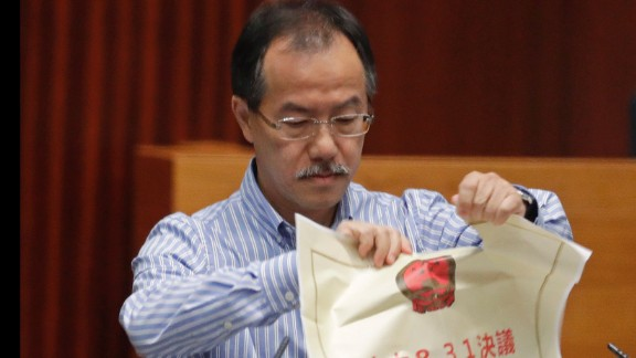 A newly elected pro-democracy lawmaker, Fernando Cheung tears an oversized mock copy of controversial, proposed anti-subversion legislation as he takes oath on Wednesday.