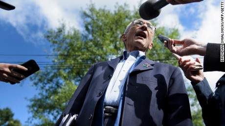 John Podesta talks to reporters as he walks to Democratic presidential nominee Hillary Clinton's Washington, DC, home October 5, 2016.