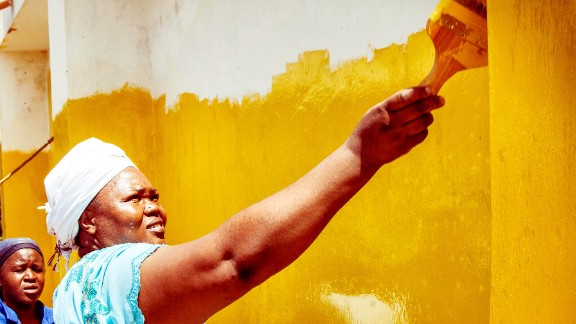 """Bishop Rose Mungafu jumped at the chance to paint her church yellow. """"For me, yellow is the color of the sun and the sun shines above everybody,"""" she said."""