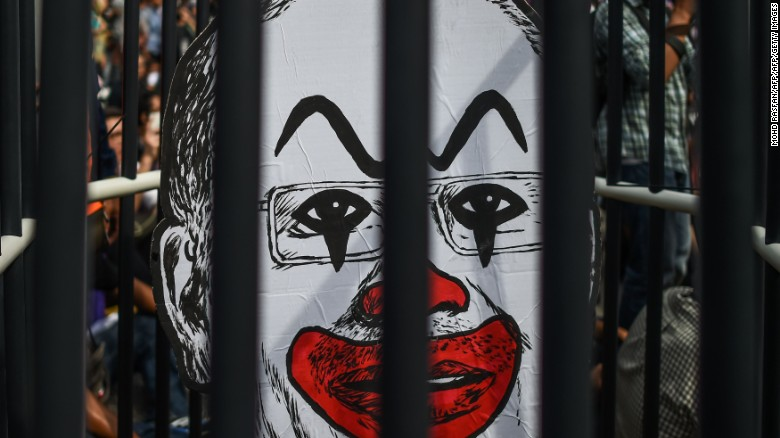 A student activist holds up a clown-faced caricature of Malaysian Prime Minister Najib Razak behind mock bars during a protest over a financial scandal involving state fund, 1MDB, in Kuala Lumpur on August 27, 2016.
