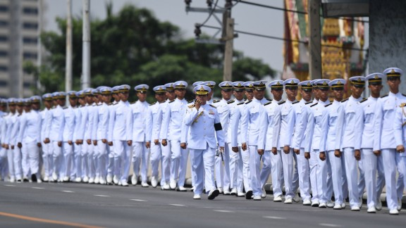 Thai army personel line up a street ahead of a procession for Thailand