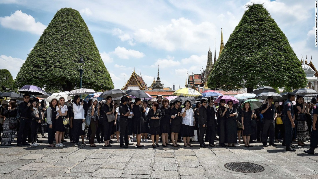 People dressed mostly in black wait outside the Grand Palace to pay respects to the King on October 14.
