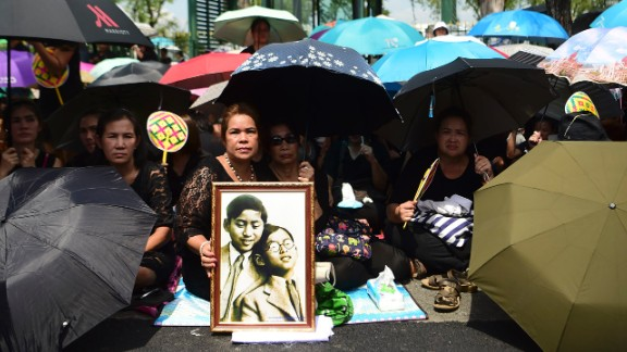 Mourners shade themselves under umbrellas while they await the procession of the King