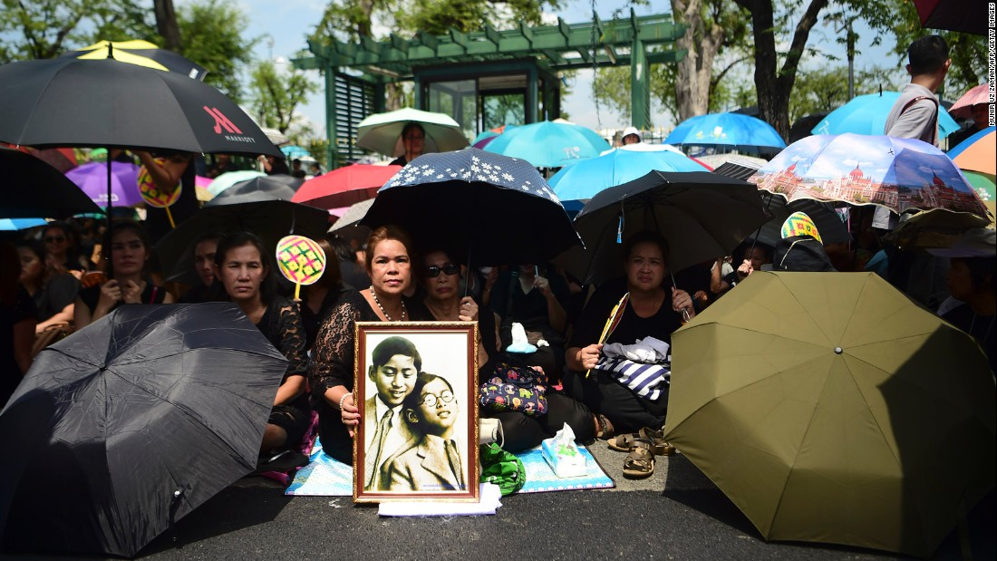 Mourners shade themselves under umbrellas while they await the procession of the King's body to the palace in Bangkok on October 14.