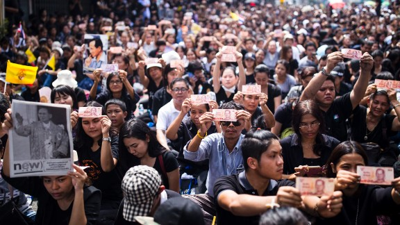 Thais gathering outside of Siriraj Hospital in Bangkok hold up baht notes with a portrait of Thailand