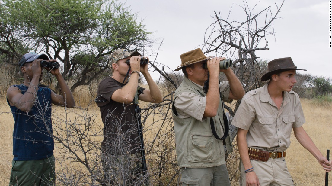 "An Austrian father and son (right) stalk their prey in the Namibian bush. Hunters use a strict discourse which creates a distance between them and their trophies. ""Sweat"" alludes to blood, while ""piece"" describes an animal."