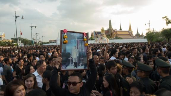 A Thai man carries high an image of Thailand