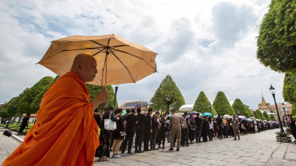 A Buddhist monk stands next to line of mourners waiting to pay their respects to the body of the late King Bhumibol Adulyadej at the Grand Palace in Bangkok, October 15, 2016.