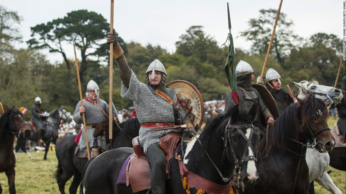 Re-enactors ride horseback dressed as Saxon fighters.