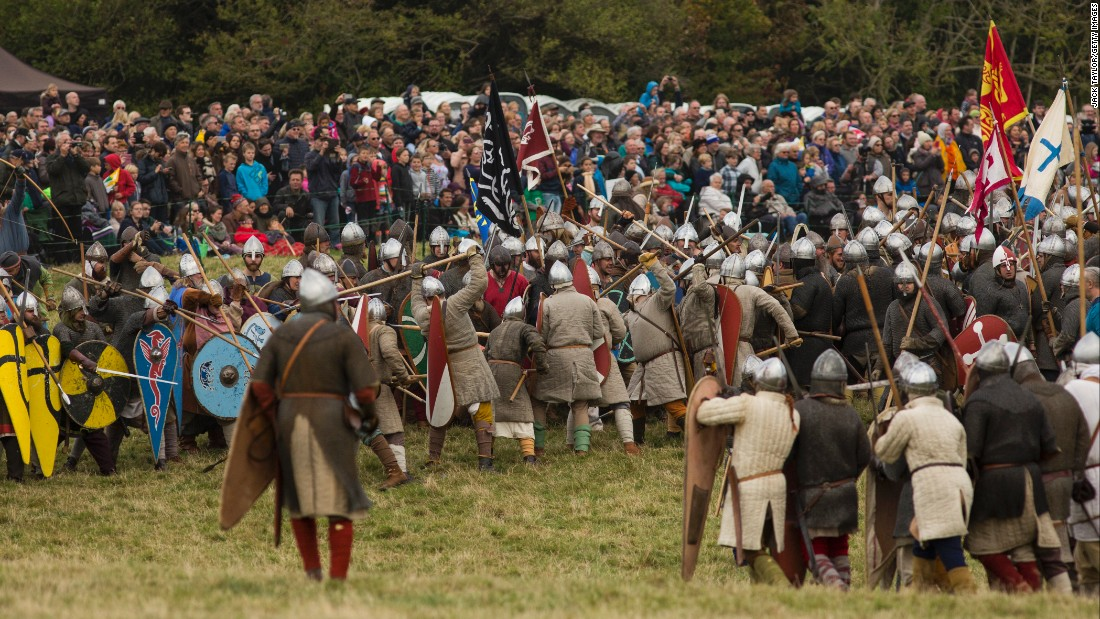 "Hundreds of re-enactors engage in ""battle"" as crowds watch the action."