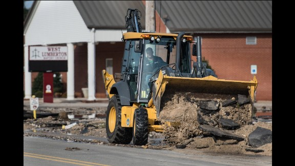 Heavy equipment is used to clear flood debris from the street in Lumberton.