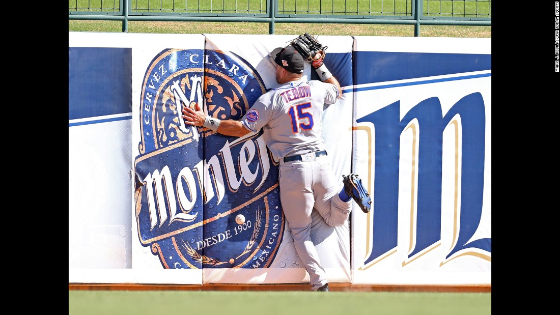 "Tim Tebow crashes into the outfield wall as he tries to catch a fly ball during a minor-league baseball game in Glendale, Arizona, on Tuesday, October 11. The former Heisman Trophy winner, who last played in the NFL in 2012, <a href=""http://www.cnn.com/2015/05/08/opinions/coy-wire-tim-tebow-chases-dream/"" target=""_blank"">is now giving pro baseball a shot.</a>"