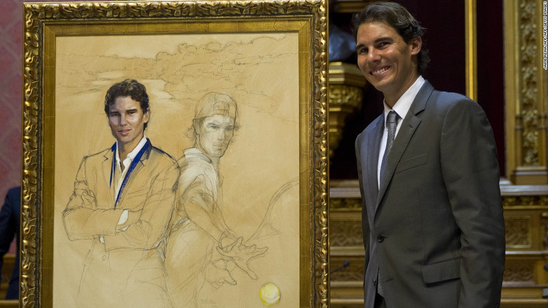 "Nadal poses next to a painting depicting himself during a ceremony in Palma where he received the title of ""Favorite Son of Mallorca"" in December 2014."