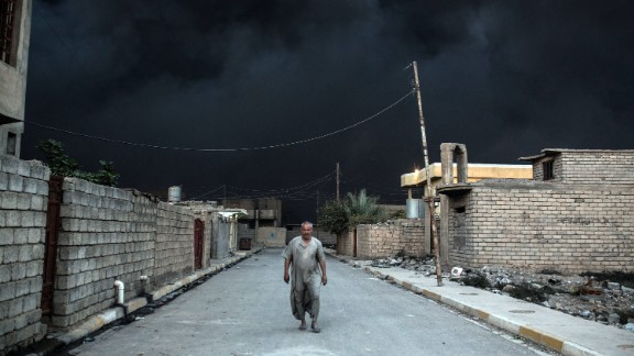 An Iraqi man escapes the thick black smoke of an oil field set on fire in Qayyarah