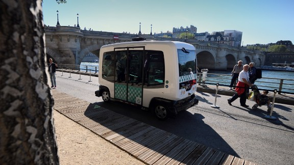 """An electric-powered driverless EZ10 minibus, seen in Paris, 2016. Developed by French firm Easymile and Dubai-based Omnix International, the bus -- known as """"The Smart Autonomous Vehicle"""" in Dubai -- drives along pre-programmed routes and features 360-degree sensors to monitor and react to its surrounds."""
