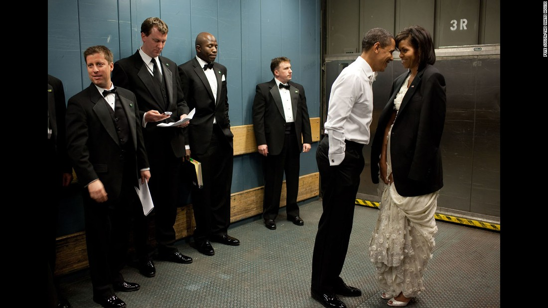 "The Obamas share a moment on a freight elevator as they head to one of the inaugural balls on January 20, 2009. ""It was quite chilly, so the President removed his tuxedo jacket and put it over the shoulders of his wife,"" White House photographer Pete Souza said. ""Then they had a semi-private moment as staff members and Secret Service agents tried not to look."""