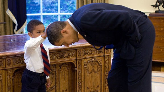 """A boy touches Obama's hair in the Oval Office on May 8, 2009. """"A temporary White House staffer, Carlton Philadelphia, brought his family to the Oval Office for a farewell photo with President Obama,"""" White House photographer Pete Souza said. """"Carlton's son softly told the President he had just gotten a haircut like President Obama, and asked if he could feel the President's head to see if it felt the same as his."""""""