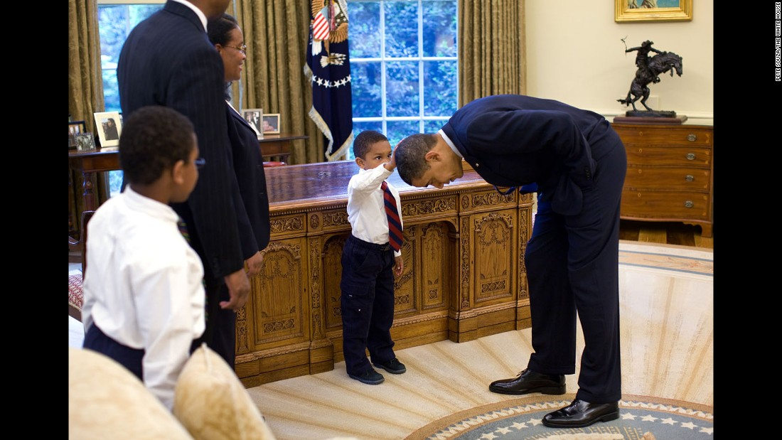 "A boy touches Obama's hair in the Oval Office on May 8, 2009. ""A temporary White House staffer, Carlton Philadelphia, brought his family to the Oval Office for a farewell photo with President Obama,"" White House photographer Pete Souza said. ""Carlton's son softly told the President he had just gotten a haircut like President Obama, and asked if he could feel the President's head to see if it felt the same as his."""