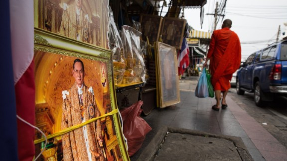 BANGKOK, THAILAND - OCTOBER 18:  A Thai monk walks by a shop that specializes in monarchy collections as sales have increased with the demand for Thai King memorabilia on October 18, 2016 in Bangkok, Thailand. Thailand's King Bhumibol Adulyadej, the world's longest-reigning monarch, died at the age of 88 in Bangkok's Siriraj Hospital on Thursday after his 70-year reign. The Crown Prince Maha Vajiralongkorn had asked for time to grieve the loss of his father before becoming the next king as nation waits for the coronation date. (Photo by Paula Bronstein/Getty Images)
