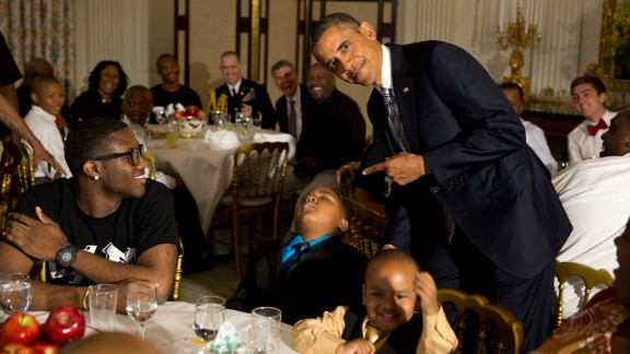 Obama takes a photo with a sleeping boy at the White House during a Father