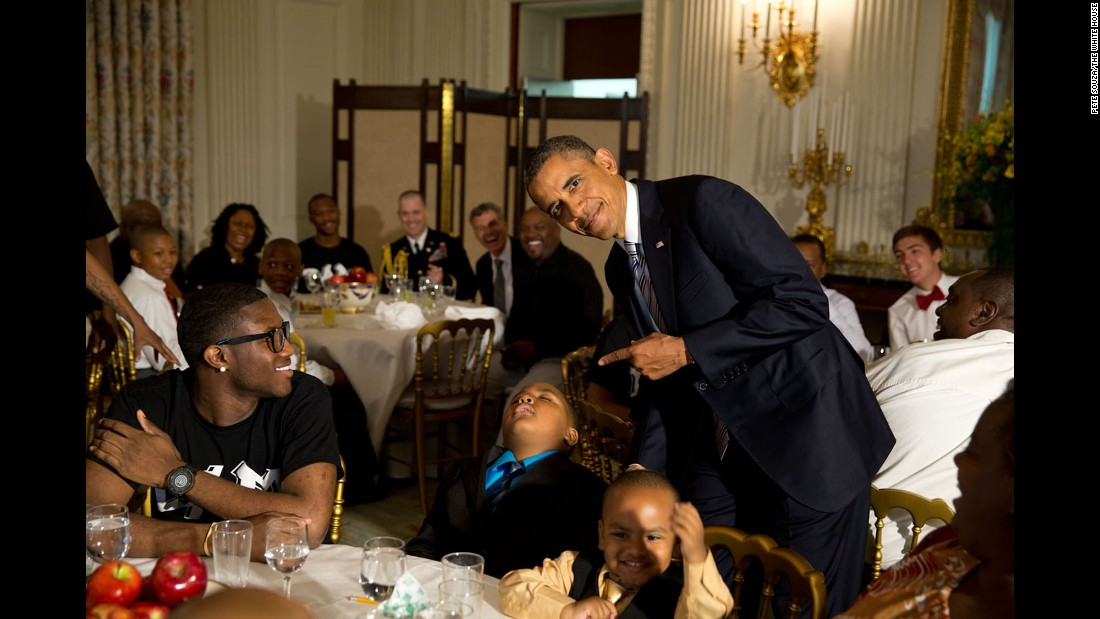 Obama takes a photo with a sleeping boy at the White House during a Father's Day ice cream social on June 14, 2013.
