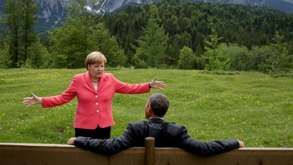 "German Chancellor Angela Merkel talks with Obama near the Bavarian Alps on June 8, 2015. Obama and other world leaders were in Germany for the annual G-7 Summit. ""Merkel asked the leaders and outreach guests to make their way to a bench for a group photograph,"" White House Photographer Pete Souza said. ""The President happened to sit down first, followed closely by the Chancellor. I only had time to make a couple of frames before the background was cluttered with other people."""