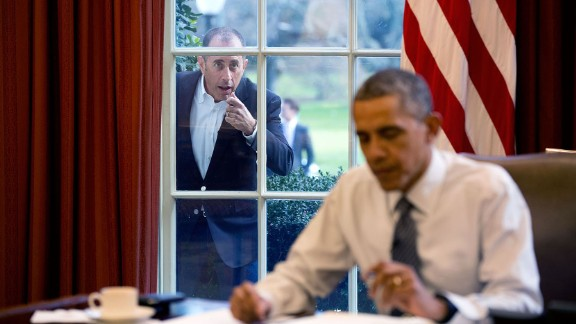 "Comedian Jerry Seinfeld knocks on the Oval Office window December 7, 2015, during a taping of his series ""Comedians in Cars Getting Coffee."" The two drove around the White House in a 1963 Corvette Stingray, drank coffee and talked politics in the episode."