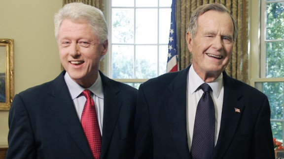 Former US Presidents George H.W. Bush and Bill Clinton smile as they leave the Oval Office on September 1, 2005 at the White House in Washington, DC.