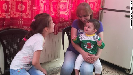 Anne plays with Rita, now nine, and her 10-month-old son Joseph, at the church in Amman, Jordan.