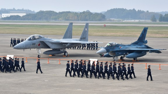 Air servicemen of the Japan Self-Defense Force walk past a F-15J/DJ fighter aircraft (L) and a F-2 A/B fighter aircraft (R) on a runway prior to a review ceremony at the Japan Air Self-Defense Force