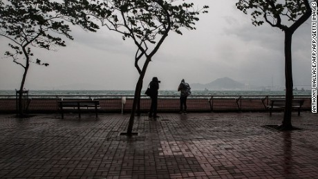 People stand on a pavement near the rough waters of Victoria Harbour as Typhoon Haima approaches Hong Kong on October 21, 2016.